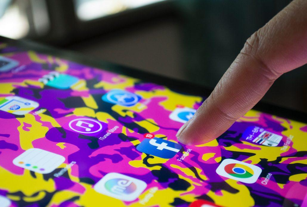 mano sujetando telefono con iconos de diferentes redes sociales en la pantalla